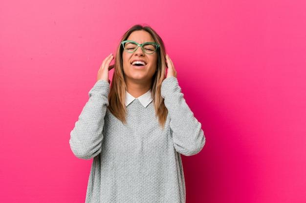 Молодая аутентичная харизматичная женщина у стены радостно смеется. концепция счастья.