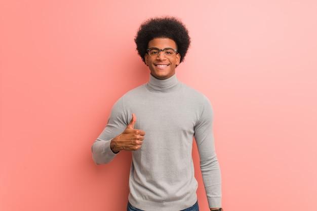 Молодой афроамериканец человек над розовой стеной, улыбаясь и поднимая палец вверх