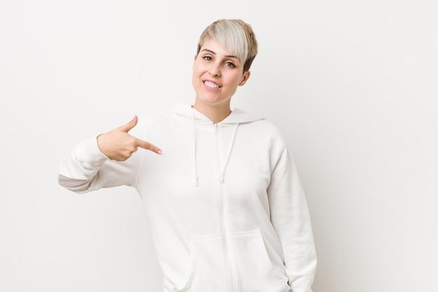 Молодая соблазнительная женщина в белом балахоне, указывая рукой на рубашку, гордо и уверенно