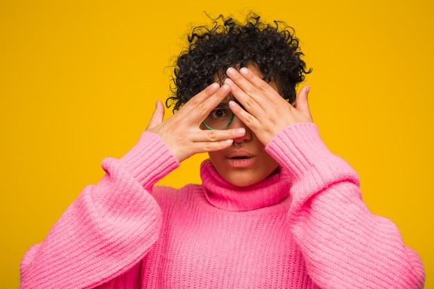 ピンクのセーターを着ている若いアフリカ系アメリカ人女性は、恐怖と緊張の指の間で点滅します。