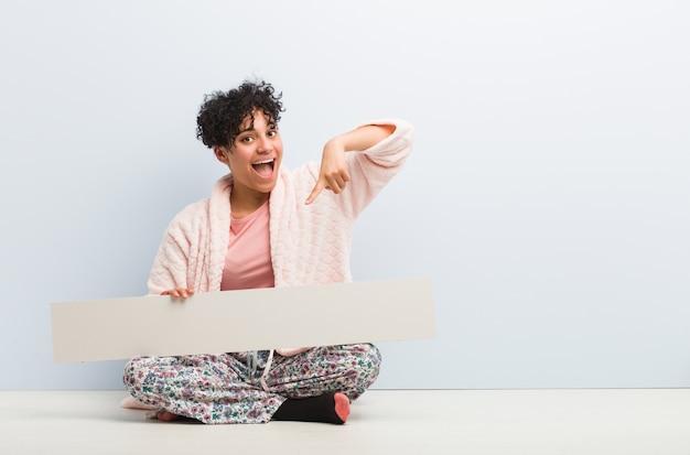 Молодая афро-американская женщина сидя с плакатом усмехаясь жизнерадостно указывая с указательным пальцем прочь.