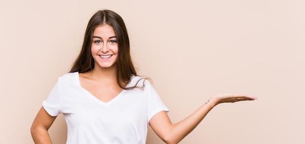 若い白人女性が手のひらにコピースペースを示し、腰に別の手を握って分離ポーズします。