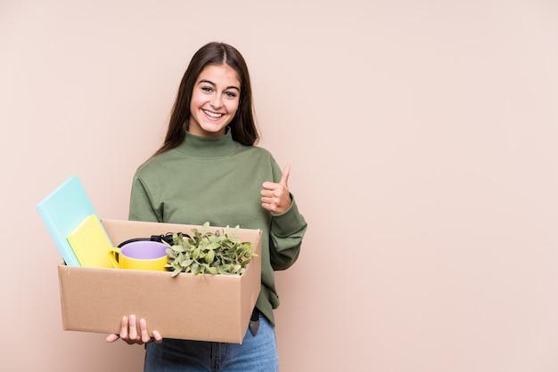 笑顔と親指を上げる分離された新しい家に移動する若い白人女性