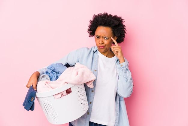 洗濯をしている中年のアフリカ系アメリカ人女性は、指で彼の寺院を指して、考えて、タスクに焦点を当てて分離しました。
