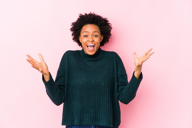 勝利または成功を祝って分離されたピンクの壁に中年のアフリカ系アメリカ人女性、彼は驚いてショックを受けた。