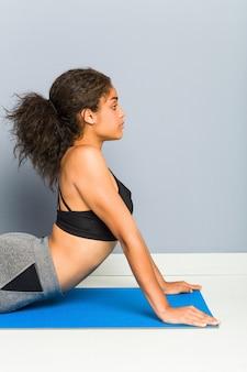 マットを使用して横になっているヨガの練習の若いアフリカ系アメリカ人のスポーティな女性