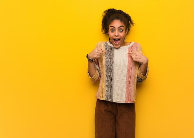 驚いた青い目を持つ若い黒人アフリカ系アメリカ人の女の子は、成功と繁栄を感じています