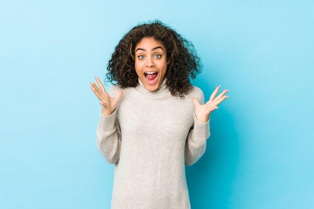 勝利または成功を祝っている若いアフリカ系アメリカ人の巻き毛の女性、彼は驚き、ショックを受けています。