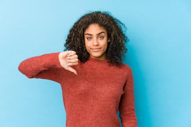 嫌いなジェスチャー、親指ダウンを示す若いアフリカ系アメリカ人の巻き毛の女性。不一致の概念。