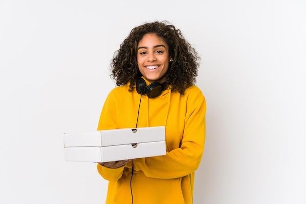 笑って、楽しんでピザを保持している若いアフリカ系アメリカ人学生の女性。