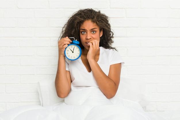 神経質で非常に不安な爪をかむ目覚まし時計を保持しているベッドに座っている若いアフリカ系アメリカ人女性。