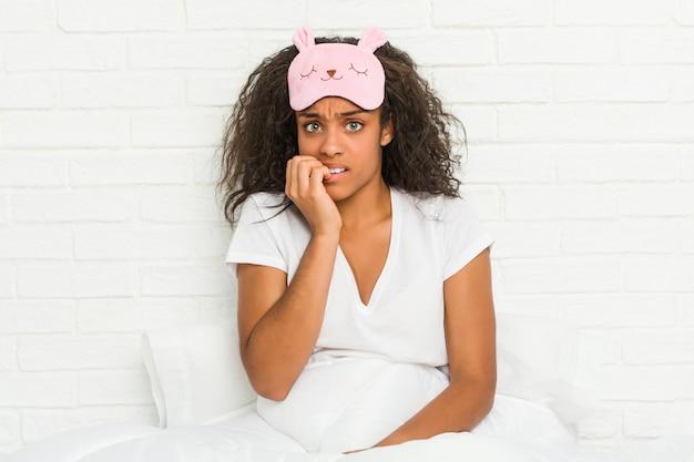 神経質で非常に不安な爪をかむ睡眠マスクを着てベッドに座っている若いアフリカ系アメリカ人女性。