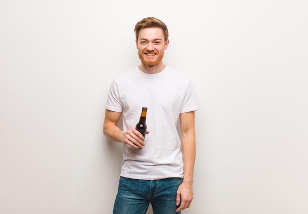 大きな赤毛の陽気な赤毛の若い男。ビールを保持しています。