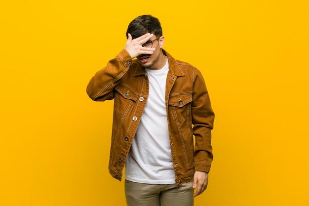 ヒスパニック系のカジュアルな若者が、顔を覆う恥ずかしい指の間で点滅します。