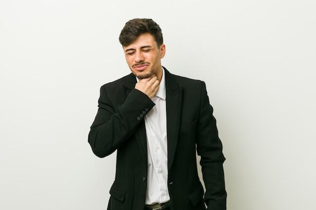 若いビジネスヒスパニック系男性は、ウイルスや感染症により喉の痛みに苦しんでいます。
