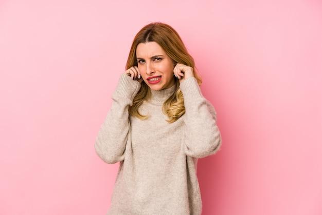 Молодая белокурая милая женщина нося свитер изолировала покрывать уши руками.