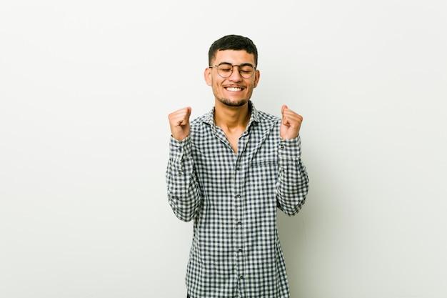 幸せな成功を感じて、拳を上げるヒスパニック青年。勝利のコンセプト。