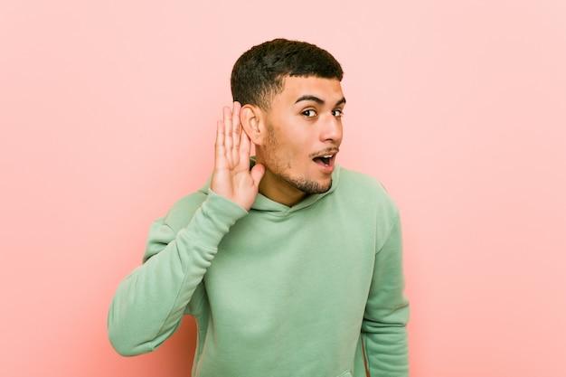Молодой испанский спортивный человек пытается слушать сплетни.