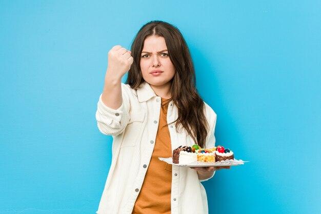 積極的な表情で拳を示す甘いケーキを保持している若い曲線の女性。