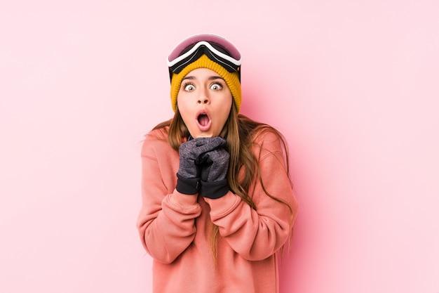Молодая кавказская женщина нося одежды лыжи изолировала молить для рта удачи, изумленного и раскрывая смотря к фронту.