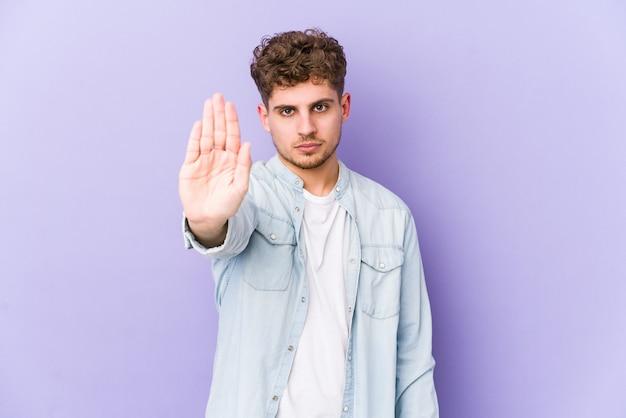 Человек молодого белокурого вьющиеся волосы кавказский изолировал положение при протягиванный знак стопа показа руки, предотвращая вас.