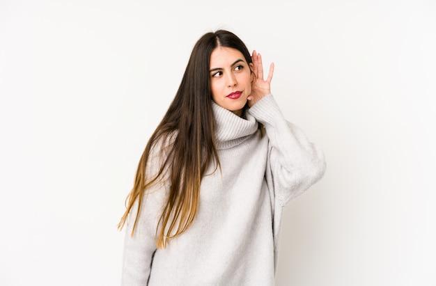 Молодая кавказская женщина изолированная на белой стене пробуя слушать сплетню.
