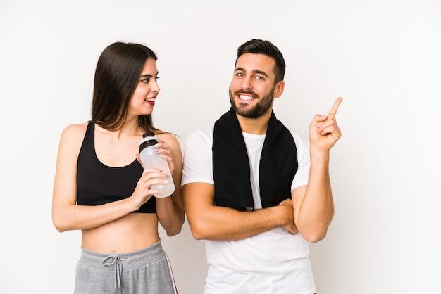 若い白人フィットネスカップルは、人差し指で元気に指している笑顔を分離しました。