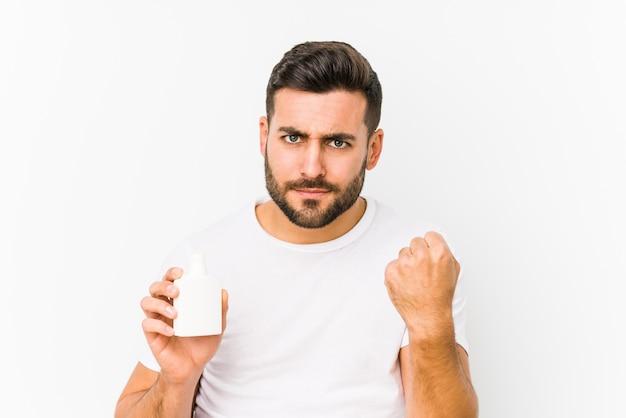 積極的な表情で拳を示す分離されたビタミンボトルを保持している若い白人男。
