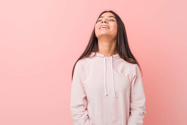 カジュアルなスポーツを着た若いかなりアラブの女性はリラックスして幸せな笑いを見せ、首を伸ばして歯を見せています。