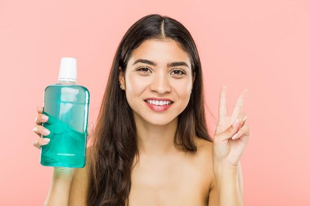 Молодая индийская женщина, держа бутылку для полоскания рта, показывая номер два с пальцами.