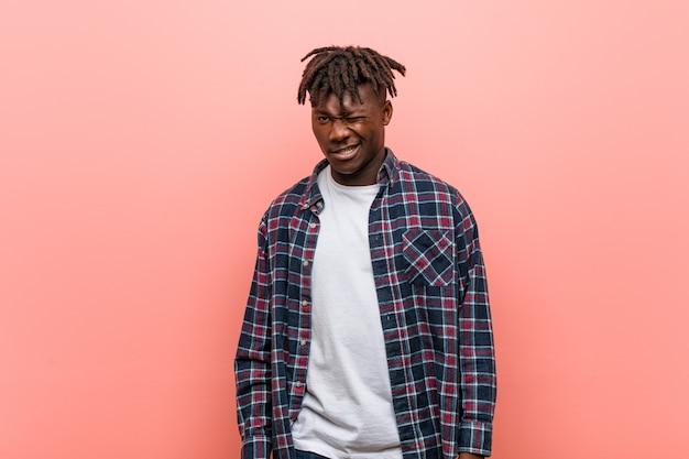 Молодой африканский темнокожий мужчина, подмигивающий, забавный, дружелюбный и беззаботный.