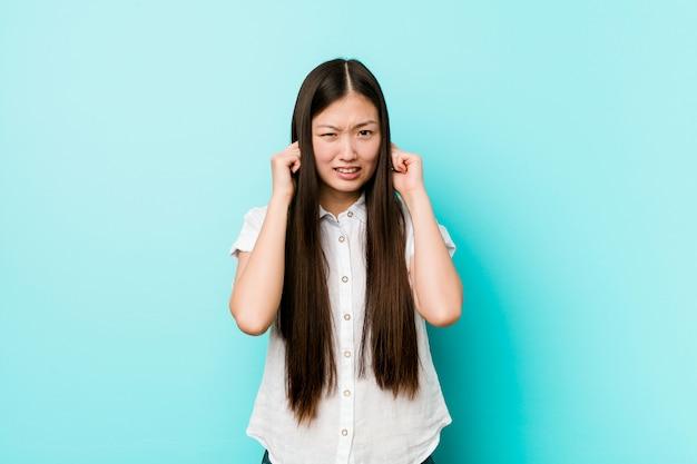 若い可愛い中国人女性の手で耳を覆っています。