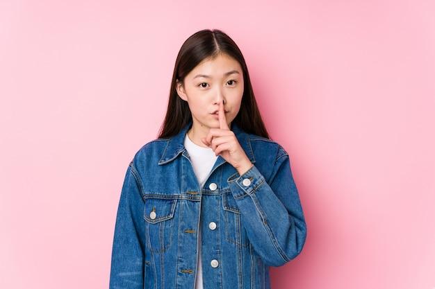 Молодая китайская женщина представляя в розовой стене изолировала держать секрет или просить безмолвие.