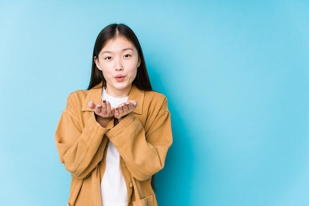 Молодая китайская женщина представляя в голубой стене изолировала складывая губы и держа ладони для посылки воздушного поцелуя.