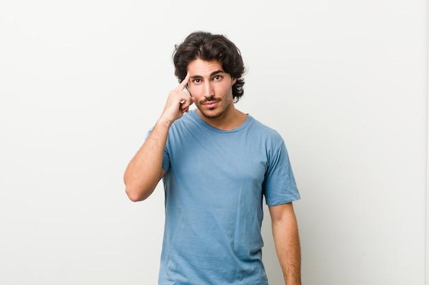 指で寺院を指して、考えて、タスクに焦点を当てた白い壁に対して若いハンサムな男。