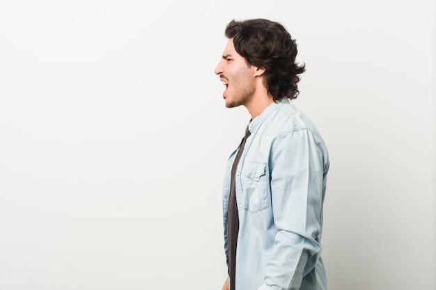 コピースペースに向かって叫んでいる白い壁に対して若いハンサムな男