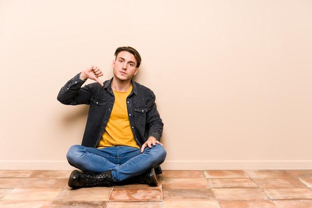Молодой кавказский человек сидя на изолированном поле показывая жест нелюбов, большие пальцы руки вниз. концепция несогласия.