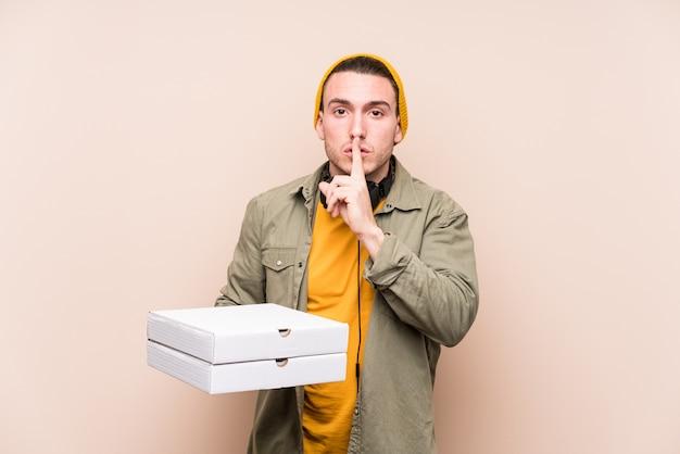Молодой человек кавказской холдинг пиццы, сохраняя в тайне или прося молчания.