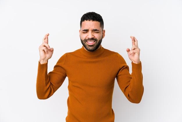 Молодой латинский мужчина на белой стене изолировал скрещенные пальцы за удачу