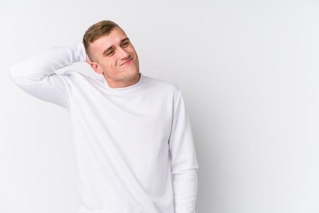 頭の後ろに触れる、考えて、選択をする白い壁に若い白人男。