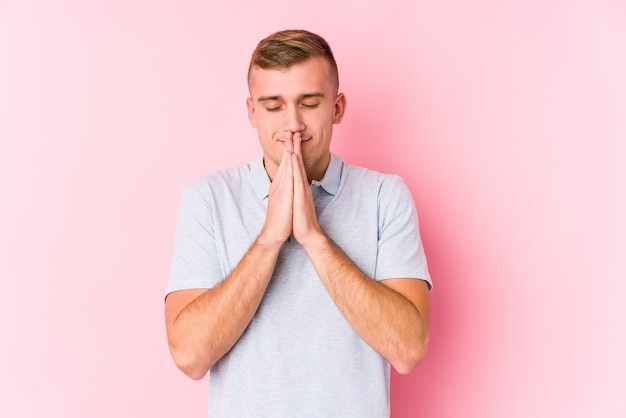 口の近くで祈って手を繋いでいる分離された若い白人男は自信を持って感じています。