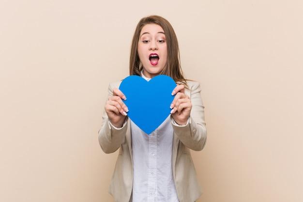Молодая кавказская женщина держа значок сердца