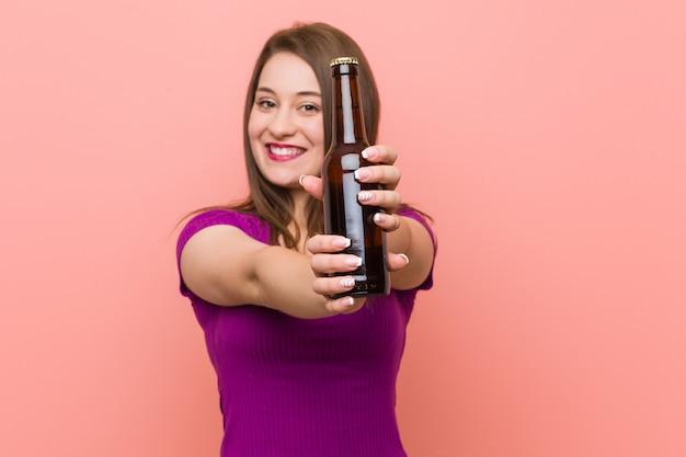 ビール瓶を保持している若い白人女性