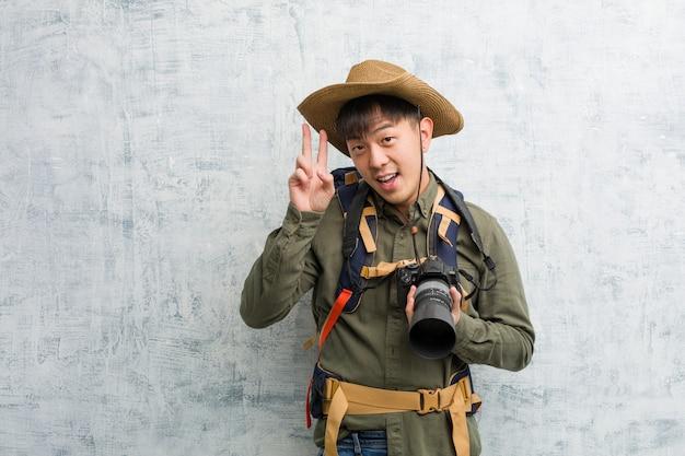 Молодой китайский исследователь человек держит камеру весело и счастлив, делая жест победы