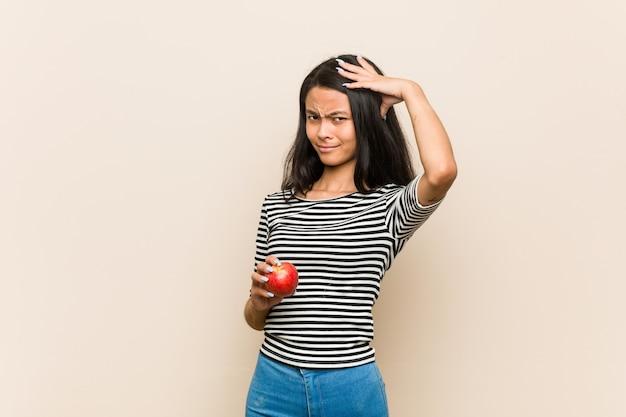 ショックを受けているリンゴを保持している若いアジア女性、彼女は重要な会議を覚えています。