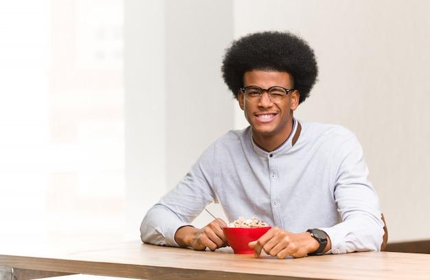 Молодой черный человек завтрака подмигивая, веселый, дружелюбный и беззаботный жест