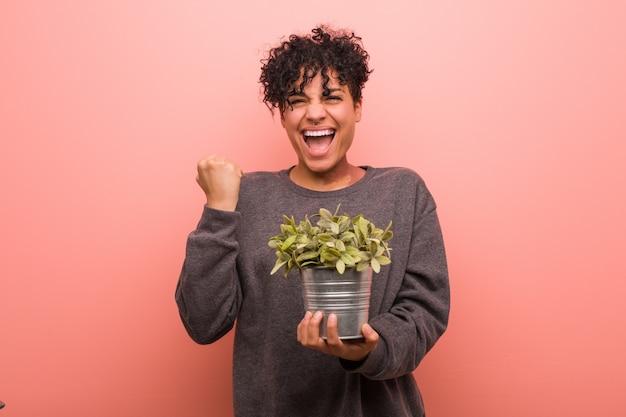勝利または成功を祝う植物を保持している若いアフリカ系アメリカ人女性