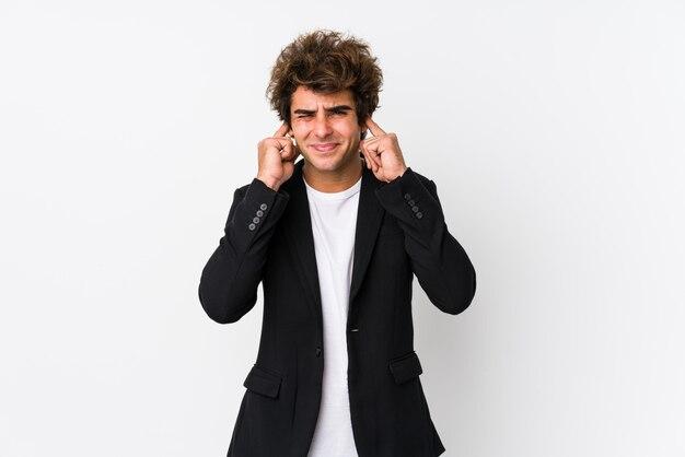 Молодой кавказский бизнесмен против белой стены изолировал покрывать уши руками.