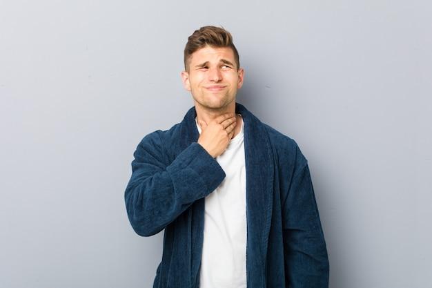 パジャマを身に着けている若い白人男性は、ウイルスや感染症のために喉の痛みに苦しんでいます。
