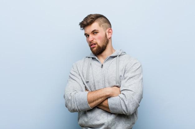 若いハンサムなフィットネス男の頭の後ろに触れる、考えて、選択をします。
